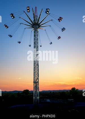 Swing ride. Star flyer. Amusement ride in sunset. - Stock Photo