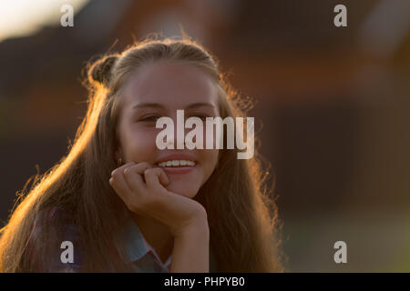 Pretty young teenage girl with a thoughtful smile resting her chin on her hand as she sits outdoors at sunset in a head shot portrait - Stock Photo