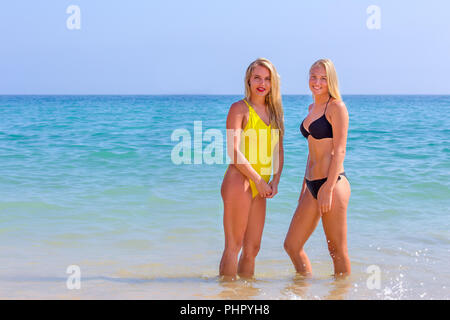 Two young women standing in blue sea water - Stock Photo