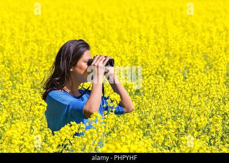Woman looking through binoculars in blooming rapeseed field - Stock Photo