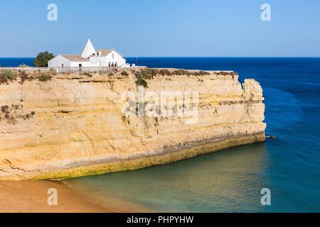 White church on steep rock in blue sea - Stock Photo