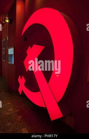 Red hammer and sickle neon sign in communist section of Warsaw Uprising Museum in Warsaw, Poland, proletarian symbol of Russian Revolution - Stock Photo