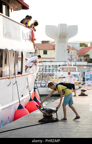 Vodice, Croatia - August 11, 2018: A cruise ship Carpe Diem arriving in Vodice and  docking. A man and a teenage boy on a pier fastening the ship rope - Stock Photo