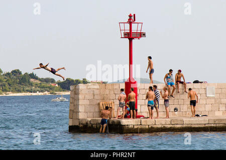 Vodice, Croatia - August 2, 2018: Young men in swimsuits standing on the pier and watching a man jumping in the sea in summer season - Stock Photo