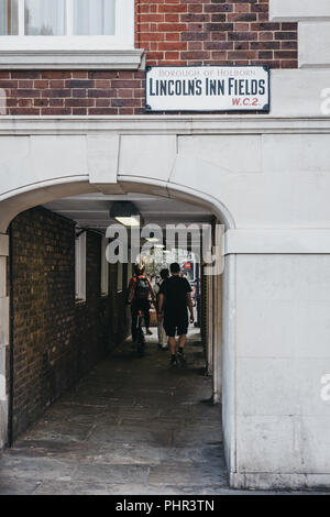 London, UK - July 24, 2018: People walking through the pedestrian tunnel on Lincoln's Inn Fields, the largest public square in London, UK. - Stock Photo