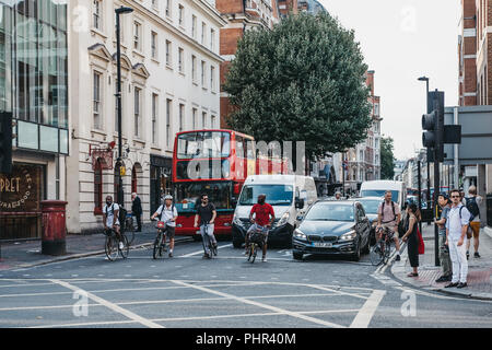 London, UK - July 24, 2018: Cyclists, cars and buses waiting for green light on Oxford Street intersection, a major road in the City of Westminster in - Stock Photo