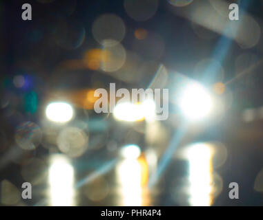 Bright white lights from cars on the night city street blurry abstract background - Stock Photo