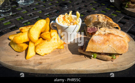 Lunchtime snack Steak  sandwich served on Ciabatta bread coleslaw and Chips - Stock Photo