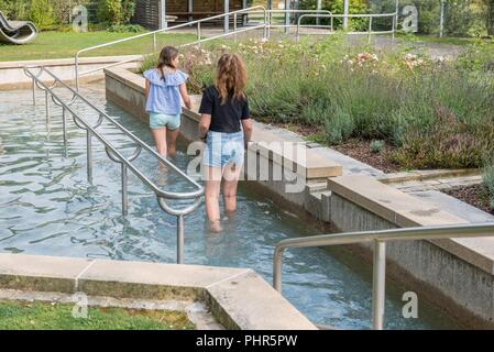 Two young girls taking a Kneipp cure in summer - Stock Photo