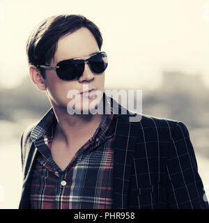 Young handsome fashion man in sunglasses outdoor - Stock Photo