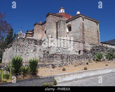 Side of San Pedro church in Mitla city, cobble road at archeological site of Zapotec culture on Oaxaca landscape, Mexico - Stock Photo