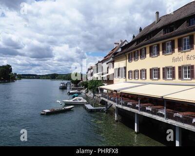 European STEIN am RHEIN town in SWITZERLAND, yellow building on Rhine River landscape in swiss canton of Schaffhausen - Stock Photo