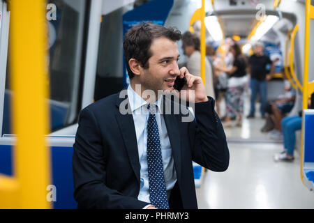 Portrait of businessman talking on his mobile phone while is going to work - Stock Photo