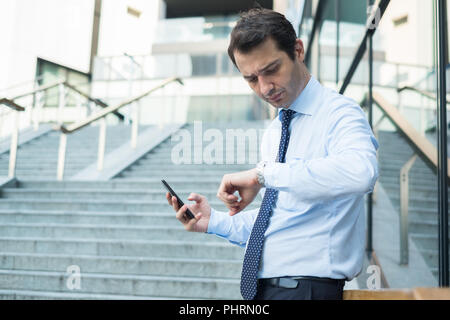 Busy businessman checking the time on his wristwatch - Stock Photo