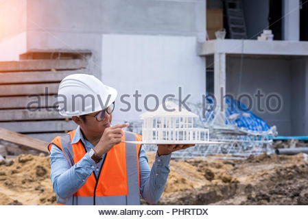 Architect civil engineer working at construction site and checking building model - Stock Photo