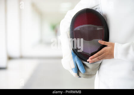 Close-up of a fencer in white fencing suit and hand holding her mask. - Stock Photo