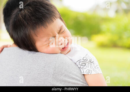 Closeup portrait of upset little girl crying on her mothers shoulder in garden background, happy young loving family, new life concept. - Stock Photo
