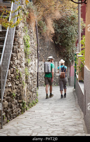 tourists enjoying a pleasant walk through the streets of manarola, italy  part of the cinque terre - Stock Photo