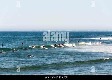 Surfers riding the waves in Malibu beach in summer time - Stock Photo