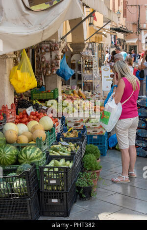 woman shopping for vegetables at a greengrocers fruit and vegetables stall on a greek market in the old town of kerkira, corfu, greece. - Stock Photo
