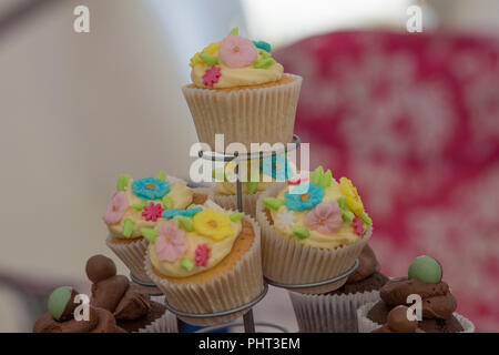 brightly coloured cup cakes decorated on a cake stand - Stock Photo