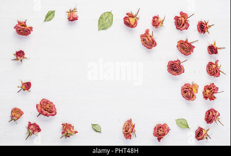 Dried roses flowers on vintage wooden table - Stock Photo