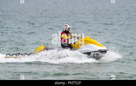 RNLI lifeguard on patrol at Bournemouth Beach in Dorset - Stock Photo