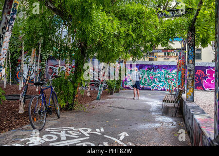 Berlin,Graffiti Corner, small park with birch trees,benches, trampoline. Surrounding buildings, benches and walls have brightly coloured graffiti tags - Stock Photo