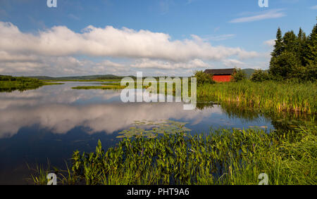 Tranquil landscape shot of a small red fishing shed on Eel River, Benton, New Brunswick, Canada. Fluffy white clouds reflected in the water. - Stock Photo