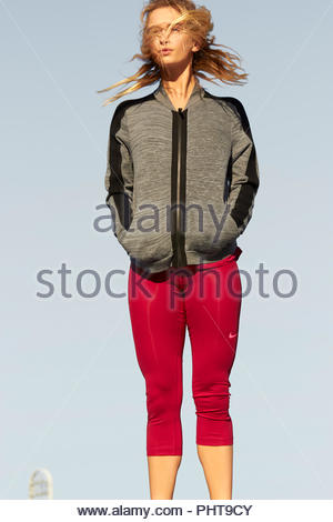Young woman wearing grey jacket and red tights - Stock Photo