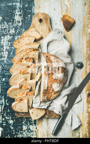 Flat-lay of freshly baked sourdough wheat bread loaf halved and cut in slices on board over linen napkin and rustic wooden table background, top view - Stock Photo