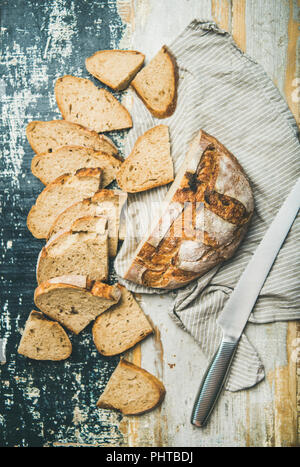 Flat-lay of freshly-baked sourdough wheat bread loaf halved and cut in slices over linen napkin and rustic table background, top view, vertical compos - Stock Photo