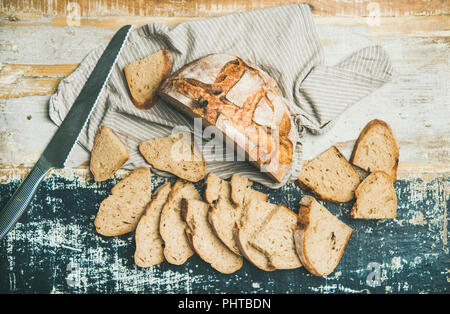 Flat-lay of freshly baked sourdough wheat bread loaf halved and cut in slices over linen napkin and rustic table background, top view, horizontal comp - Stock Photo