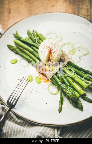 Healthy breakfast. Green asparagus with soft-boiled egg, leek and bacon served in white plate over rustic wooden background, selective focus - Stock Photo