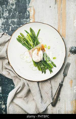 Healthy breakfast. Flat-lay of green asparagus with soft-boiled egg, leek and bacon served in white plate over linen napkin and rustic wooden backgrou - Stock Photo