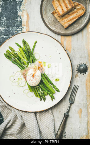 Healthy breakfast. Flat-lay of green asparagus with soft-boiled egg, leek and bacon served in white plate and grilled bread slices over rustic wooden  - Stock Photo
