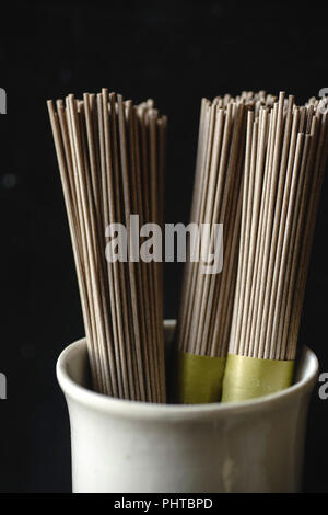 Close up of soba noodles, bamboo steamer and asian cuisine props on dark background