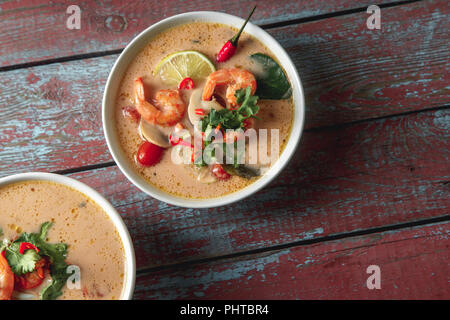 Traditional thai soup tom yum with shrimps and mushrooms, served with fresh lime slices. Top view, rustic wooden background - Stock Photo
