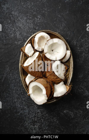 Cracked coconuts arranged in metallic tray on dark textured background. - Stock Photo