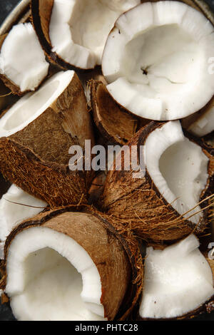 Close up view pf cracked coconuts arranged in metallic tray - Stock Photo