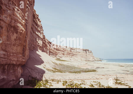 Towering red sandstone cliffs at Angola's coast line in the Namib Desert. - Stock Photo