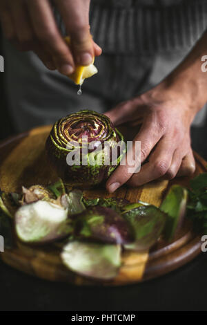 Drops of lemon squeezed on to an artichoke - Stock Photo