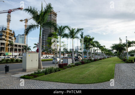 Luanda, Angola - April 28 2014: Luanda's promenade with palms and construction of modern high rise buildings at sea side of capital. - Stock Photo