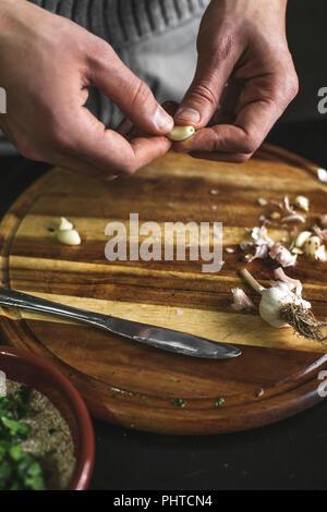 A man holding a garlic clove - Stock Photo