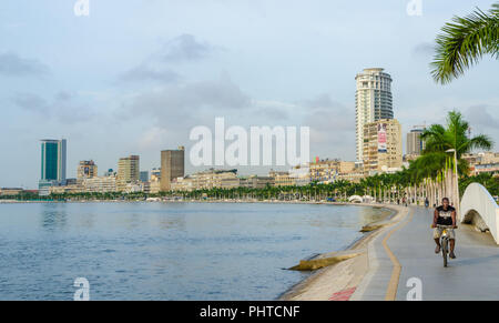 Luanda, Angola - April 28 2014: Bay of Luanda with seaside promenade and man on bicycle on overcast day. - Stock Photo