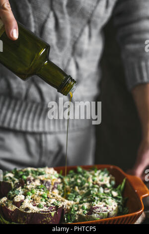 A man pours homemade olive oil on artichokes - Stock Photo