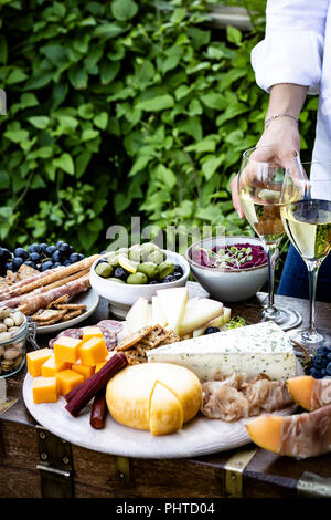 Meat and Cheese Platter served with wine outdoors - Stock Photo