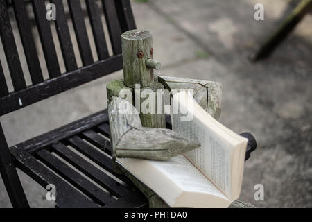 Wooden figure sat on a garden chair outside reading a book - Stock Photo