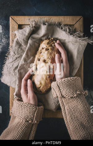 Christmas cake. Female hands make traditional German festive baking. Wholegrain dough stollen preparation on linen napkin over dark blue texture backg - Stock Photo