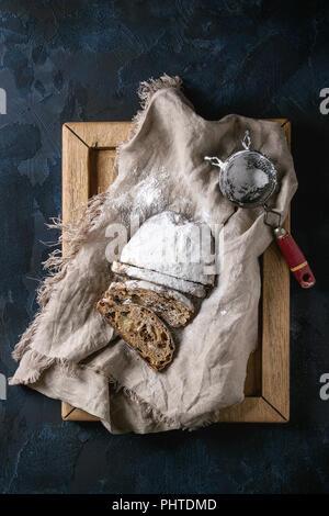 Sliced Christmas cake, traditional German festive baking. Wholegrain stollen with raisins and sugar powder on linen napkin, wooden tray, vintage sieve - Stock Photo